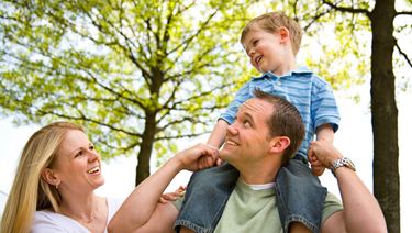 Personal Banking - Smiling family of three in park. Child is riding on father's shoulders.