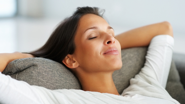 CDs and IRAs - Woman relaxing on couch with hands behind head and eyes closed.