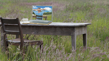 Old barn wood desk with chair in the middle of tall grass field with laptop on the desk. Laptop pictures a man sitting at the same desk in the same field relaxing.