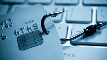 Phishing Attacks - close up of fishing hook in credit card on top of keyboard.