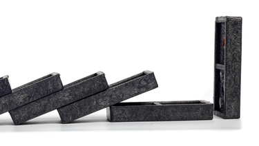 Black plastic dominoes having collapsed on each other except the last one in the row is still standing.