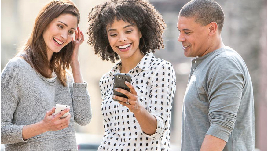 Three young adults smiling and looking at smartphone being help by woman standing in the middle.