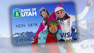 Image of family looking at camera in ski clothes on top of a mountain, captured on a personalized debit card