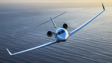 Aircraft owner trust.  Private jet flying over a body of water.
