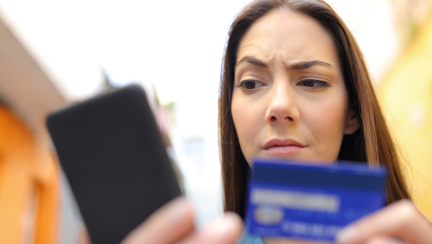 Suspicious woman looking at phone holding credit card.
