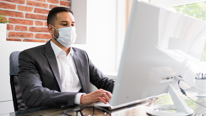 Man wearing a mask working on a computer