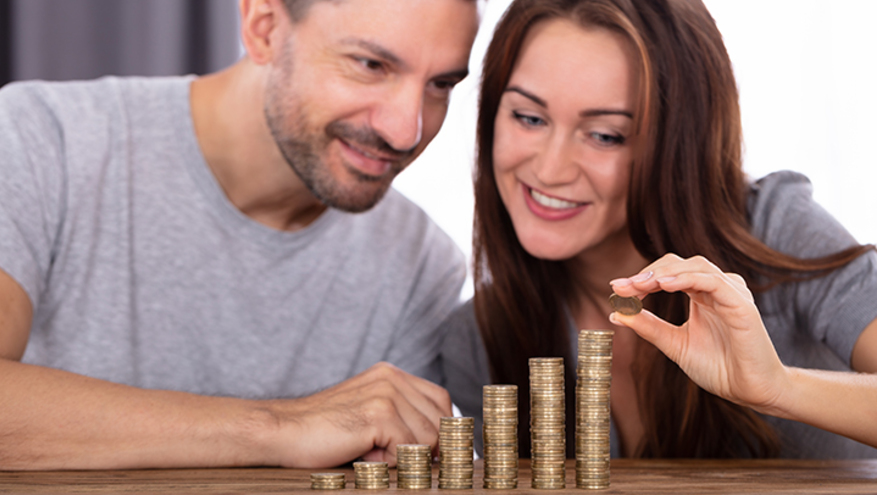 Photo of a young man and a woman stacking coins on a wooden table