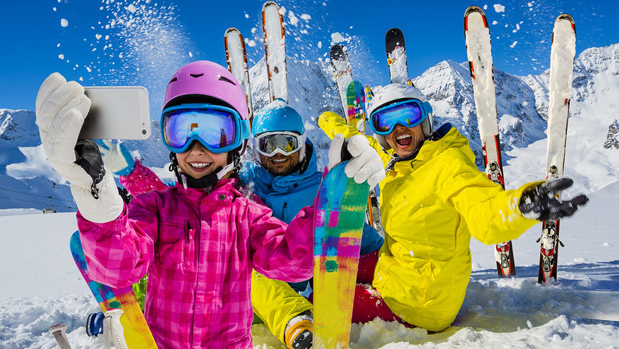 A family of three on the ski slopes smiles while a young girl takes a group selfie