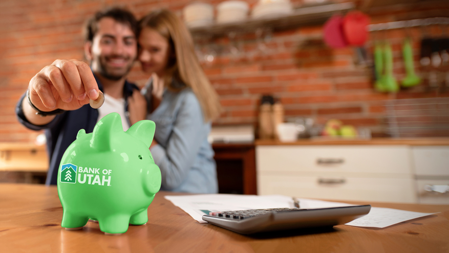 Happy couple in background reaches to put a coin into a green Bank of Utah piggy bank.